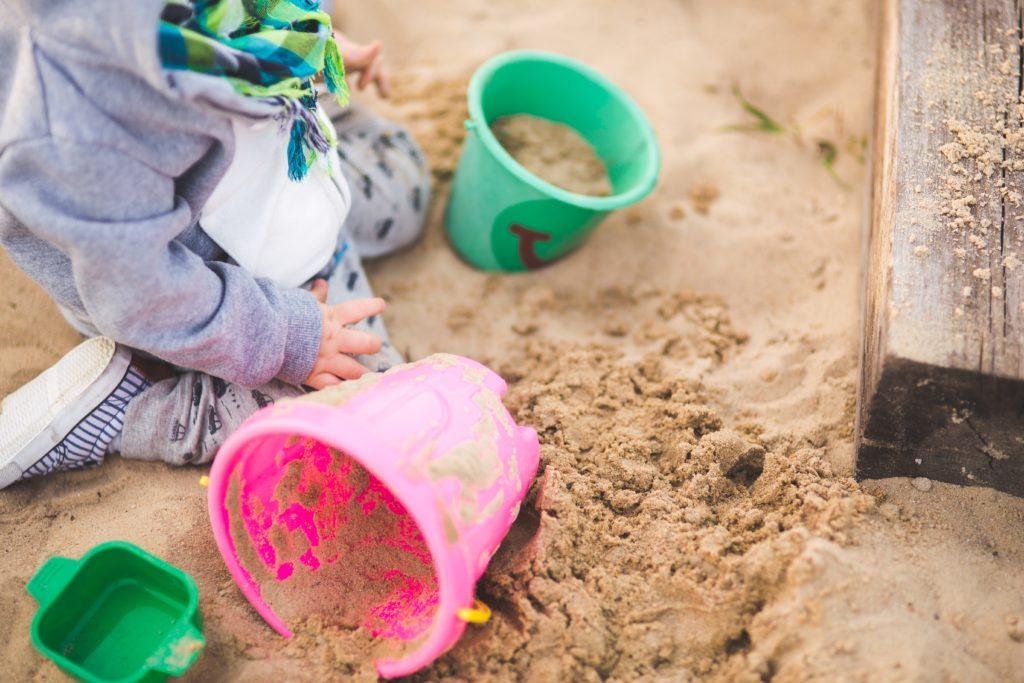 Kleinkind spielt im Sandkasten