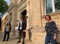 Zwei Lehrkräfte und ein Azubi stehen vor der Christlichen Akademie für Gesundheits- und Pflegeberufe Halle